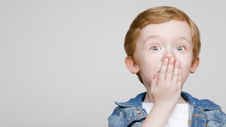 Lapsi pitää kättä suun edessä. Lapset ja hammaslangan käyttö.