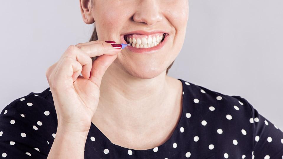 Hammasvälien puhdistus hammasväliharjalla.